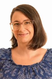 Astrid Pintzinger im Portrait. Sie hat lange dunkelbraune Haar, Stirnfransen, eine große Brille mit zartrosa Fassung. Sie lächelt in die Kamera.