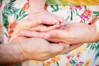 3 Hände übereinander mit der Handfläche nach oben halten ein Babyfüßchen